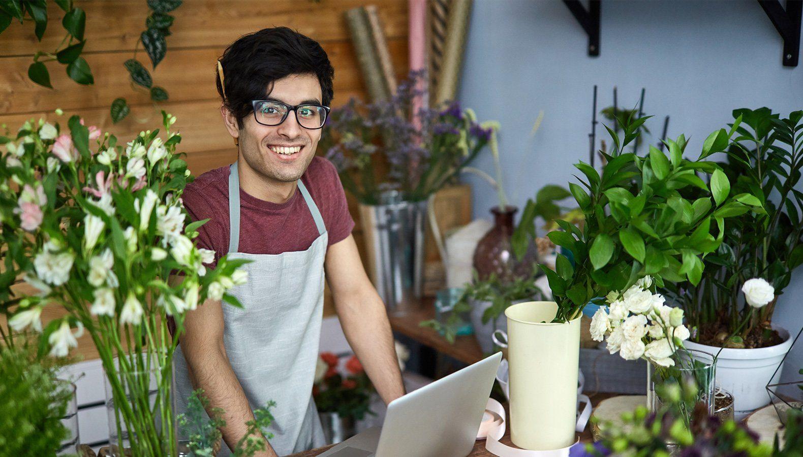 Ein Florist lächelt in die Kamera, während er am Bindetisch voller Blumen in der Filiale steht und ein Laptop aufgeklappt vor sich stehen hat.