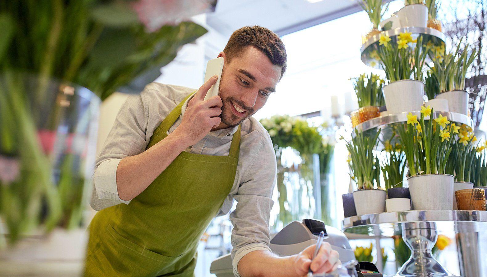 Ein Florist bestellt über das Telefon neue Ware von einer Bestellliste.