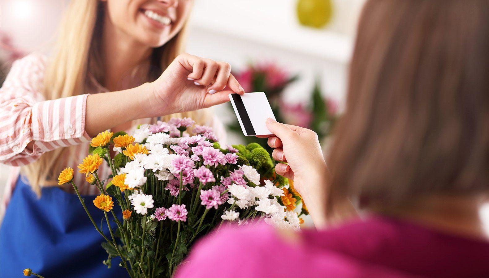 Eine Floristin nimmt eine Kreditkarte einer Kundin entgegen, die ihren Blumenstrauß bezahlen möchte.