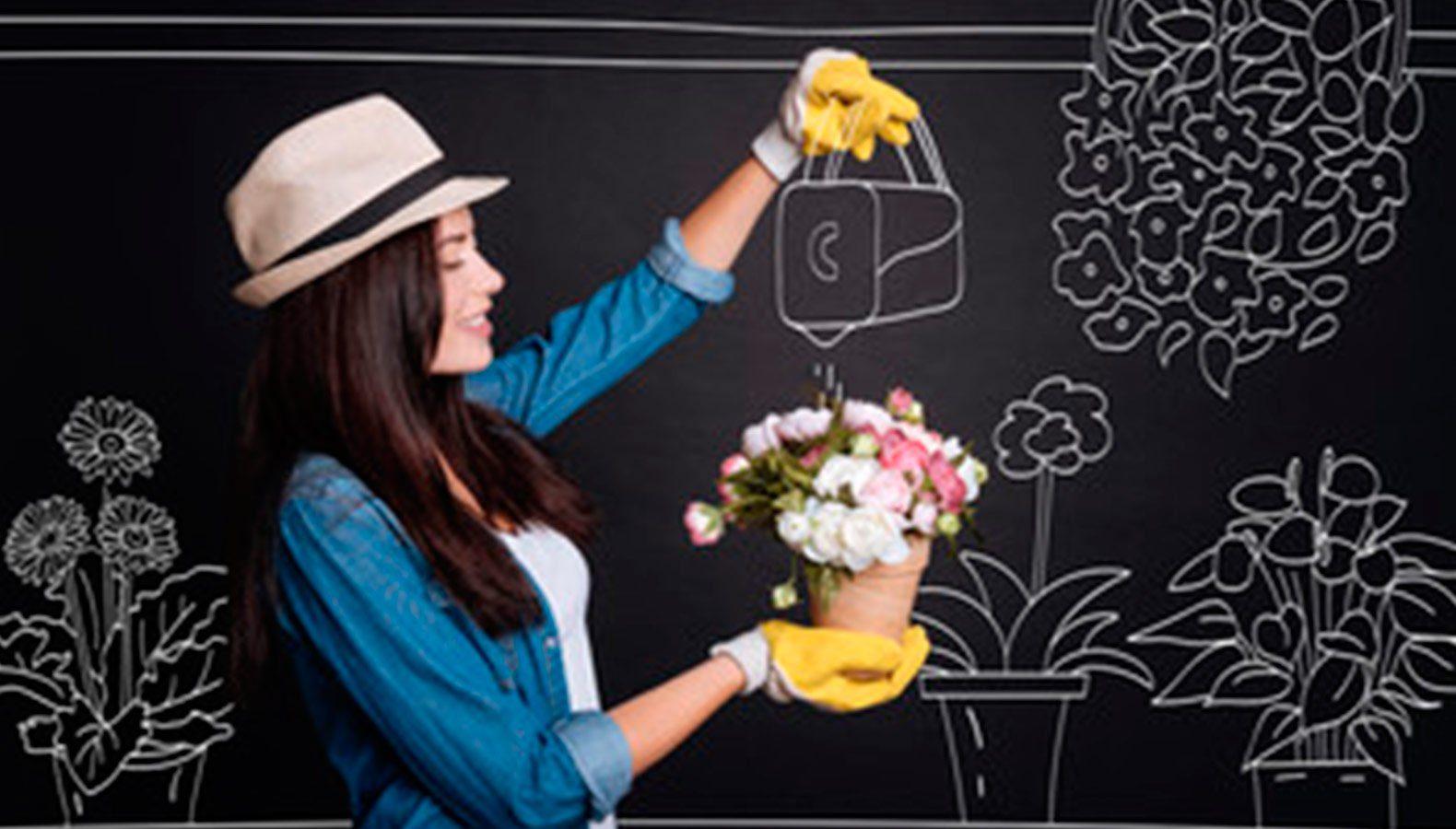 Floristin tut so, als würde sie Pflanzen mit einer an die Kreidetafel gemalten Gießkanne gießen