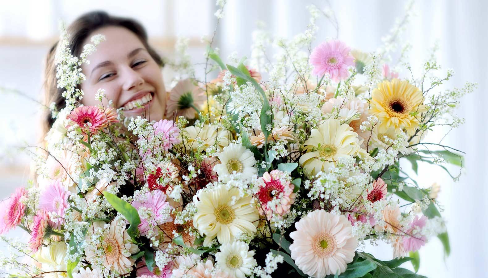 Eine Floristin präsentiert mit vollem Stolz ihren gebundenen Wiesenstrauß.