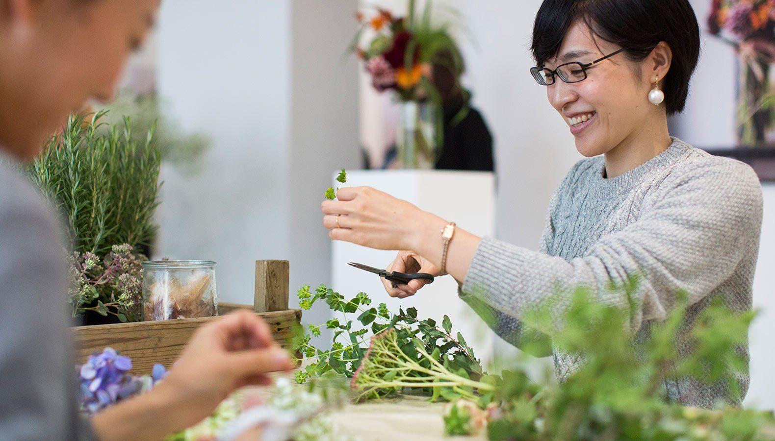 Nahaufnahme einer Floristin bei einem Workshop zum Binden von Blumen.
