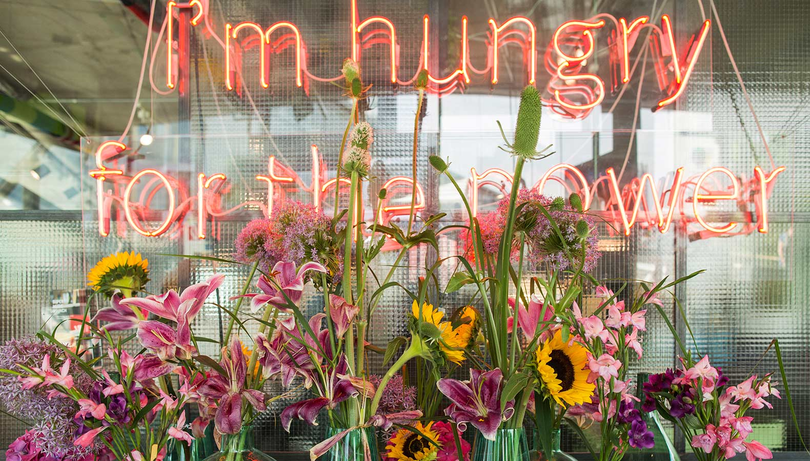 Einzelstielblumen vor einem Neon Schriftzug, auf dem steht: