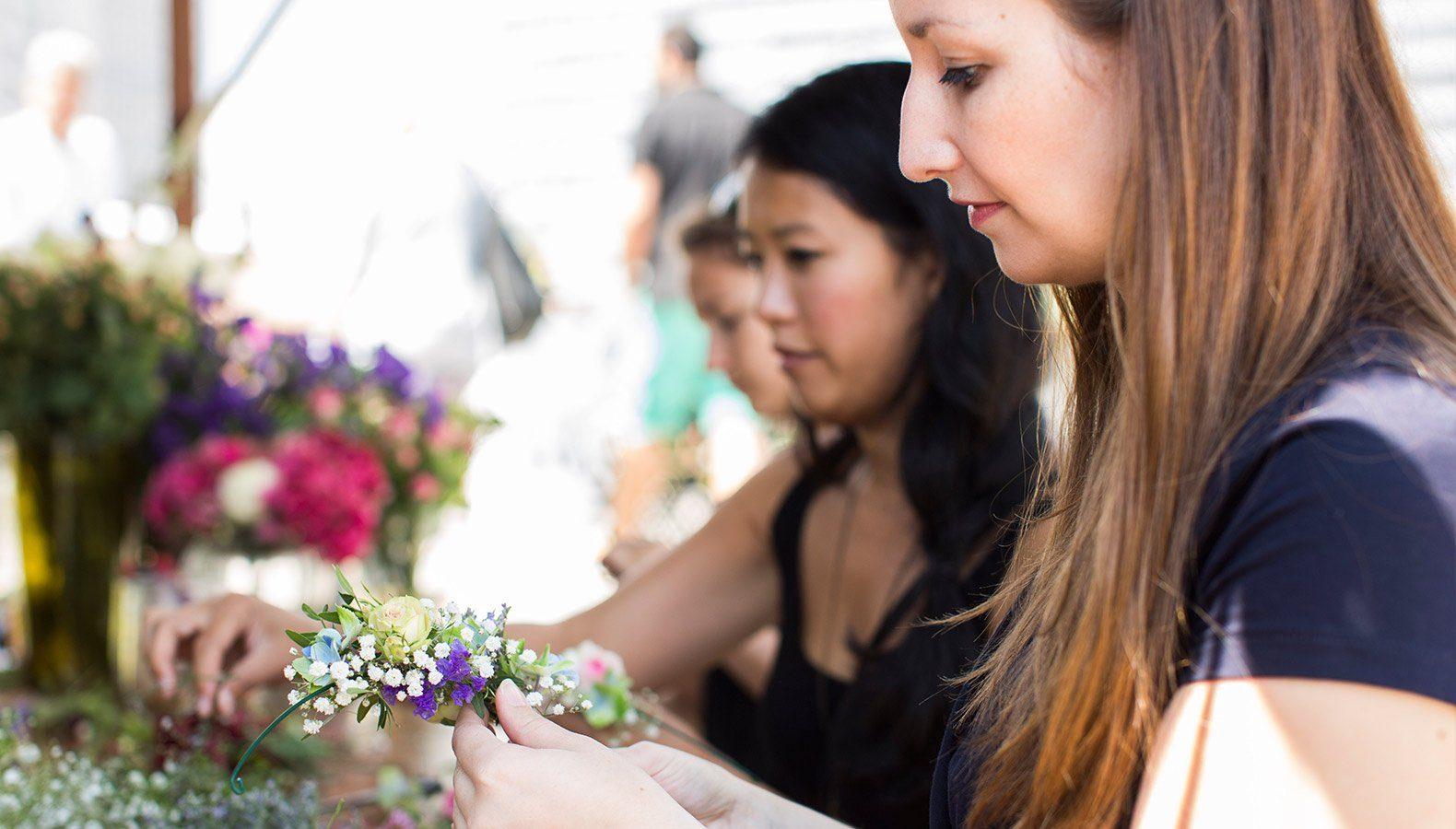Zwei Floristikauszubildende wählen aus Ware Blumen aus, die sie in einen Strauß verbinden.